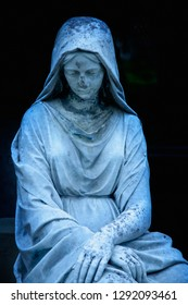 Virgin Mary statue. Vintage sculpture of sad woman in grief. Religion, faith, suffering, love concept