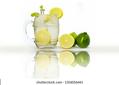 Virgin Mint Julep isolated on white in a transparent glass isolated on white with fresh lemons and mint or mentha leaves.