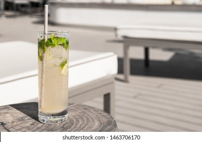 Virgin Mojito with paper straw on a wooden table near a luxury deck chair. Summer vacation drink.