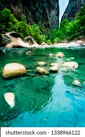 Virgin River, Zion National Park, Utah, USA. Boulders in turquoise blue water with green trees and red rocks of Zion  NP background. Environmental policy, ecology or landscape protection concepts