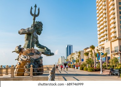 VIRGINIA BEACH, VIRGINIA - JULY 13, 2017:  People on the 3-mile long oceanfront boardwalk near the King Neptune statue, a popular picture spot area for tourists.