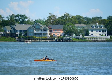 Virginia Beach, U.S.A - June 30, 2020 - The view of the waterfront homes and a kayak on Owl's Creek on a hot summer day