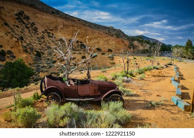 Virginia City, NV / USA - 08-16-2016: Rusty old vintage car was turned into outdoor sculpture sprouting dead trees festooned with beer bottles.