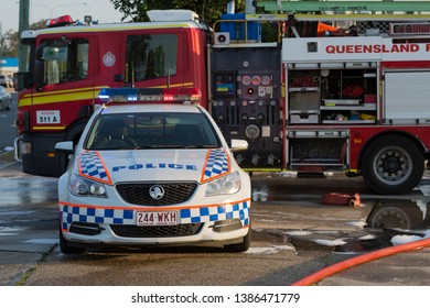 VIRGINIA, QUEENSLAND - SEPTEMBER 24, 2017: A Queensland Police Car is parked in front of a Queensland Fire Truck at the scene of a large industrial factory fire.