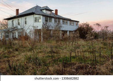 Virginia, USA - December 17, 2018: Front of a broken and abandoned two story white American plantation mansion house after the US housing crisis
