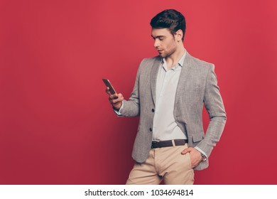 Virile, harsh, modern man  holding hand in pocket, having smart phone in hand, checking email, texting sms, using wifi, 3G internet with serious concentrated expression standing over red background