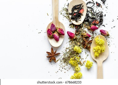 Virious kinds of herbs in wooden spoons on white table background top view mockup