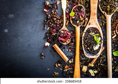 Virious kinds of tea in wooden spoons on black table