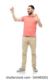 virtual, augmented reality and people concept - happy man in polo t-shirt touching something imaginary over white background