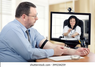 Virtual doctor explains intravenous injection technique to middle aged bearded man in the office. She points out his fist should be clenched. Horizontal shot.