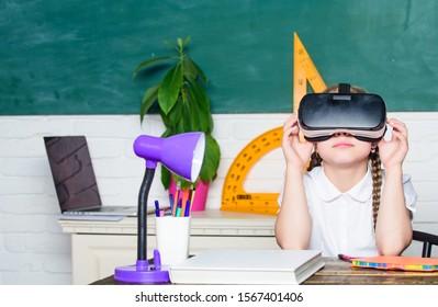 Virtual education. Child cute pupil wear hmd vr glasses. Studying in virtual reality. Modern technology. Interesting lesson. Virtual teaching. Homeschooling online. Girl kid study in virtual school.