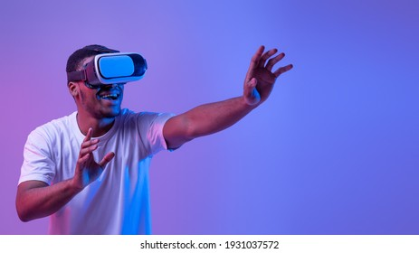 Virtual Experience. Excited African American Man In neon Lighting Wearing VR Headset, Touching Air While Playing Video Game, Amazed Black Guy Standing Over Purple Background, Panorama With Copy Space