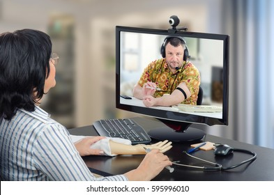 Virtual female doctor has just explained how to make an intravenous injection with training arm and now oversees telehealth patient on-line. Mature man in aloha shirt is ready to inject