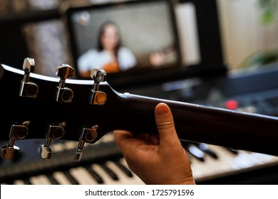 virtual guitar lesson. female musicians play together online in isolation because of the coronavirus pandemic