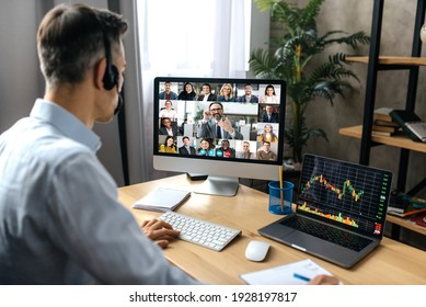 Virtual meeting, video call. Successful adult businessman have conversation with multiracial business colleagues by video call using a computer while sitting at his workplace