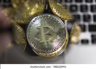 Virtual money silver bitcoin under a magnifying glass on the background of heap of coins