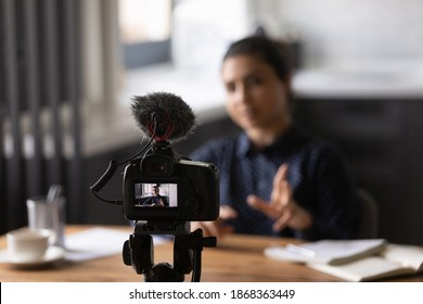Virtual public speaking. Mixed race lady teacher trainer shooting video lecture at home office using digital camera fixed on holder. Young indian female vlogger influencer recording filming content