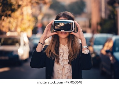 Virtual Reality 3D Video Glasses VR Headset tested by an excited young beautiful girl dressed in a office outfit amazed by augmented reality on the street with beautiful autumn sun light colors