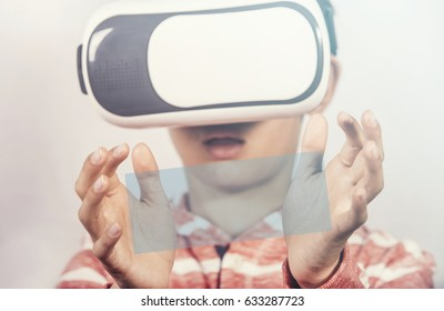 Virtual reality experience concept. Boy wearing VR glasses with copy space between his hands. (Selective focus image with shallow depth of field)