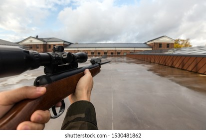 virtual reality game and violence concept - POV of male hands shooting with air rifle outdoors