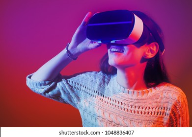 Virtual reality glasses giving amazing gaming experience. Amazed woman with goggles touching air. VR concept. Banner.