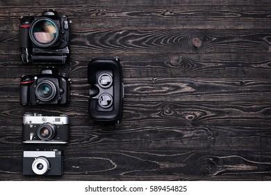 Virtual reality glasses, retro and modern digital camera on dark wooden table.Top view/Retro camera,DSLR camera,VR glasses