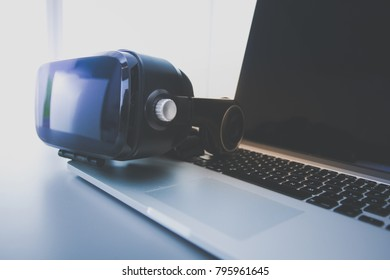Virtual reality goggles on desk with laptop. business. 3d technology
