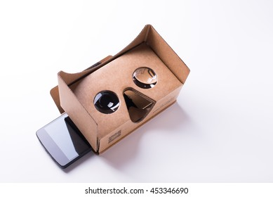 virtual reality headset from pre-cut cardboard and bi-convex lenses by Google, over white background with Google Nexus phone inside, horizontal with copy space area. Taken on July 2016, Vancouver, BC.