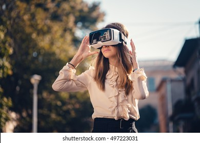 virtual reality headset, virtual reality, VR glasses, augmented reality, VR goggles - happy young girl with virtual reality headset or 360 glasses stay sitting on the street excited by 3D video