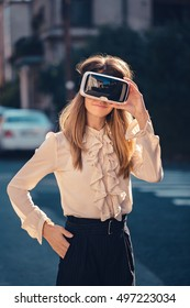 virtual reality headset, virtual reality, VR glasses, augmented reality, VR goggles - happy young girl with virtual reality headset or 3d glasses stay sitting on the street intersted by 360 image
