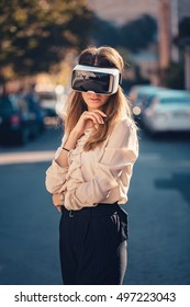 virtual reality headset, virtual reality, VR glasses, augmented reality, VR goggles - disappointed young girl with virtual reality headset or 3d glasses stay sitting on the street nostalgic about vr