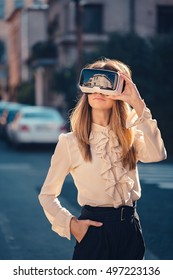 virtual reality headset, virtual reality, VR glasses, augmented reality, VR goggles - happy young girl with virtual reality headset or 3d glasses stay sitting on the street interested by 360 image