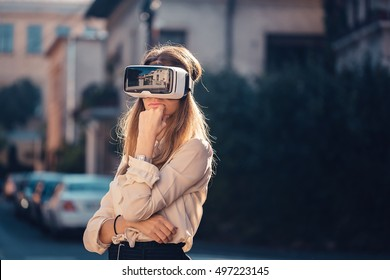 virtual reality headset, virtual reality, VR glasses, augmented reality, VR goggles - curious young girl with virtual reality headset or 3d glasses sitting on the street interested about 360 video