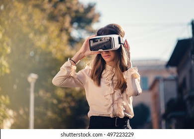 virtual reality headset, virtual reality, VR glasses, augmented reality, VR goggles - young girl with virtual reality headset or stay sitting on the street excited for testing augmented reality
