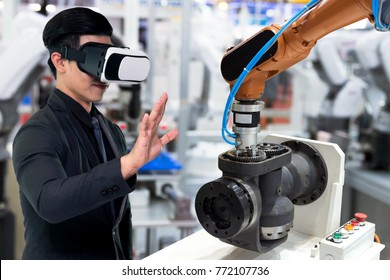 Virtual reality technology in industry 4.0. Business man suit wearing VR glasses to see AR service , Thermal Monitoring motor for check destroy part of smart robot arm machine in smart factory.