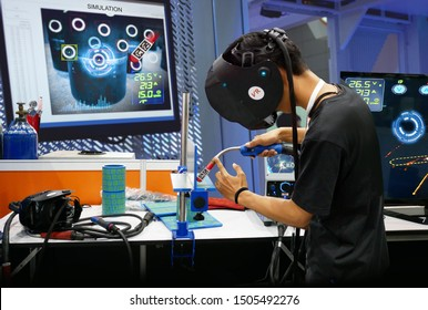 Virtual reality technology in Steel industry 4.0. Man wearing VR glasses to see simulate welding steel pipe for training, measurement and analytic to monitor screen in smart factory.