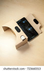 Virtual reality (VR) cardboard headset with smartphone on the table. VR glasses.