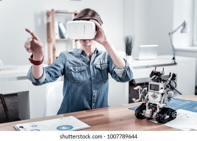 Virtual reality. Young woman raising hands and sitting at her workplace while looking forward