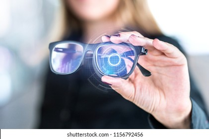 Virtual screen smart glasses with futuristic high tech interface. Woman holding spectacles with nanotech interface. Augmented reality vision with modern eyewear. Future innovation with IOT and VR.