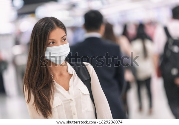 Virus mask Asian woman travel wearing face protection in prevention for coronavirus in China. Lady walking in public space bus station or airport.