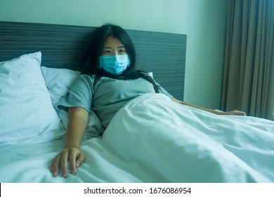 virus outbreak - young beautiful sad and worried Asian Chinese woman wearing medical face mask in quarantine and lockdown at home in panic as prevention vs coronavirus infection