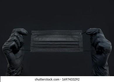 virus protection gloves and mask. Hands in black gloves hold a medical mask . black background.