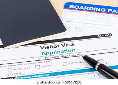Visa application form with blue passport, pen, and boarding pass
