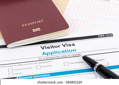 Visa application form with red passport and pen