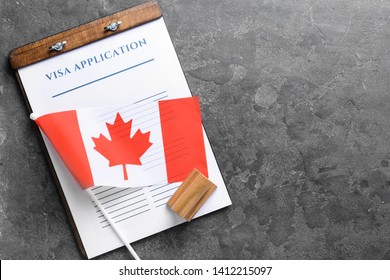 Visa application form, stamp and Canadian flag on table. Concept of immigration