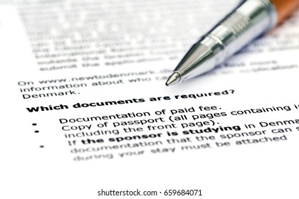 Visa application requirement list with silver ballpoint
