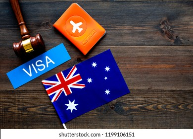 Visa to Australia concept. Text visa near passport cover and australian flag, hammer on dark wooden background top view copy space