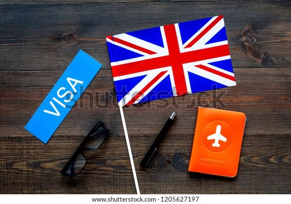 Visa to Britain concept. Text visa near passport cover and british flag on dark wooden background top view