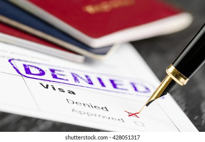 Visa form close up, fountain pen and denied stamped on a document. Soft focus.