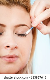 Visage, beauty concept. Closeup portrait of woman face getting her eye makeup done with cotton buds